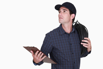 electrician carrying extension lead with clipboard