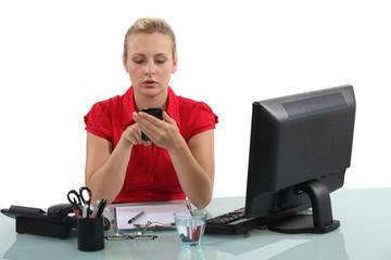 Blond receptionist typing text message