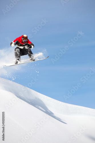 Man performing jump on snowboard