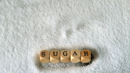 Dice spelling sugar falling into pile of sugar