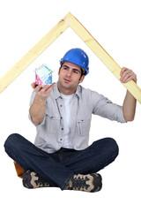 A carpenter presenting a miniature house made of euro bills.