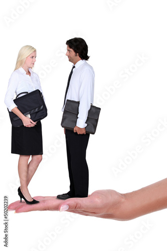 Business couple standing on a woman's hand