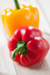 Vertical shot of fresh bell peppers on wooden boards, close-up