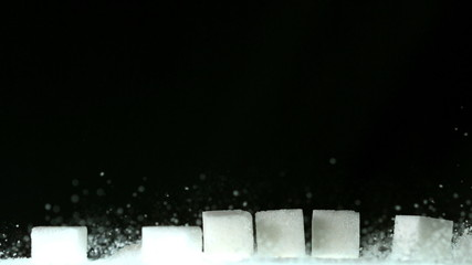 Sugar cubes falling onto pile of sugar