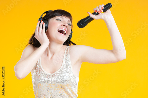 Expressive woman singing with a mike over yellow background