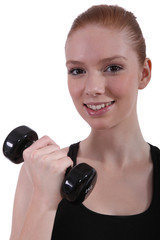 Cheerful woman with dumbbell