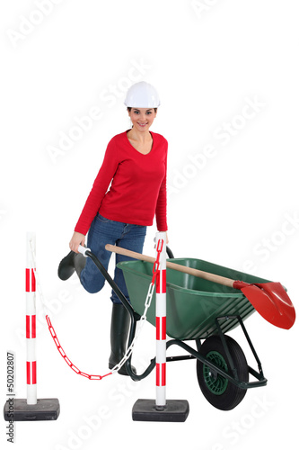Tradeswoman pushing a wheelbarrow