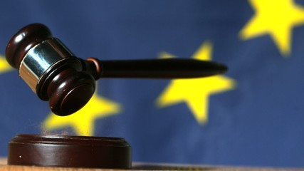 Gavel falling with european union flag in background