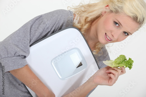Woman holding a scale and a lettuce leaf