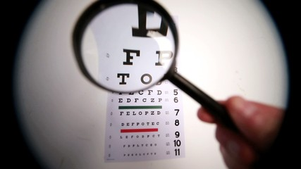 Someone holding magnifying glass up to eye test