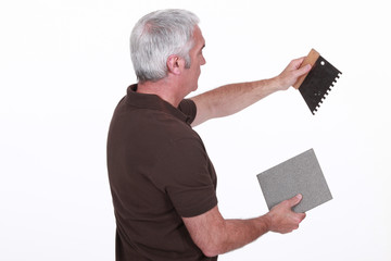 craftsman holding a tile and a tool