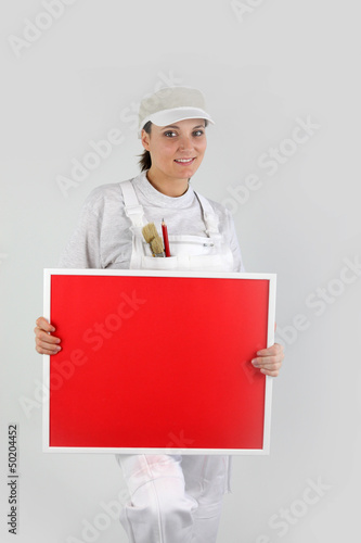 A woman painter holding up a red board