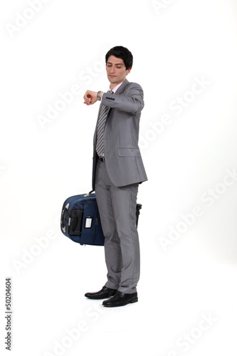 Businessman with suitcase looking at wrist watch