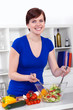 young woman preparing healthy salad in her modern kitchen