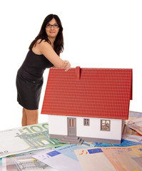 Woman based on a small house with banknotes