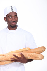Baker with an armful of baguettes