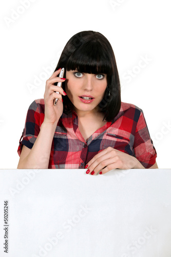 Woman on a cellphone with a board left blank for your message