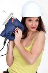 foxy female carpenter holding sander machine