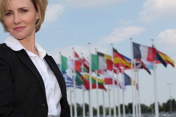 A woman looking at us with European flags in the background.