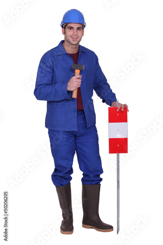 Construction worker standing with a mallet and traffic sign