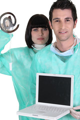medical workers holding a laptop and an at sign
