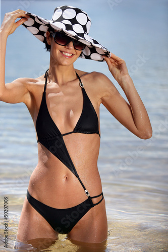 sexy brunette in black bikini with assorted sun hat