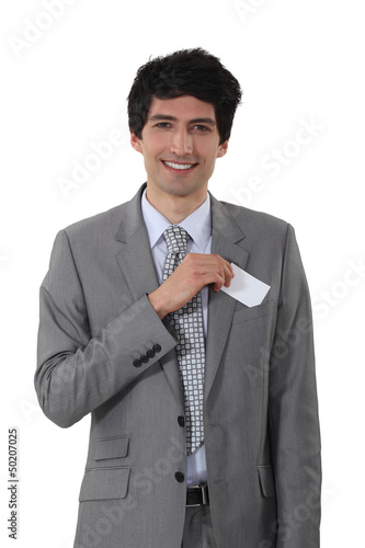 Young businessman removing business-card from pocket