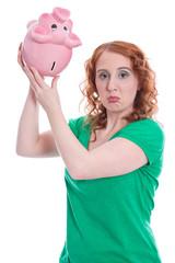Junge Frau hat Geldprobleme - isoliert in Grün mit Sparschwein