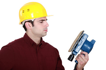 Woodworker looking at a sander
