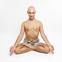 young man practicing yoga on white background, meditating in lot
