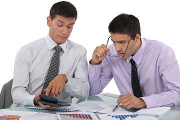 Businessmen scrutinizing financial results