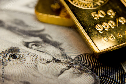 Close-up of a 20-dollar banknote and gold bullions