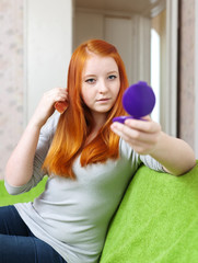 red-haired teen girl combing  hair