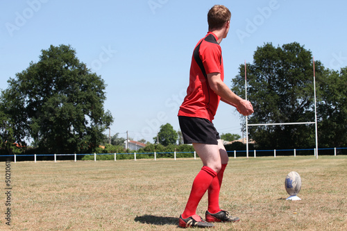 A rugbyman practicing his kick.
