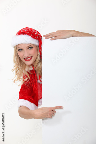 woman wearing a Santa suit and holding an advertising board