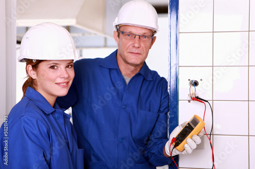 electrician and his colleague checking an electrical outlet