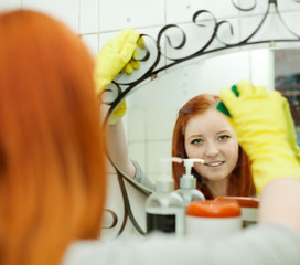 Teenager cleans mirror with sponge