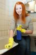 Young girl cleans bathtub in bathroom