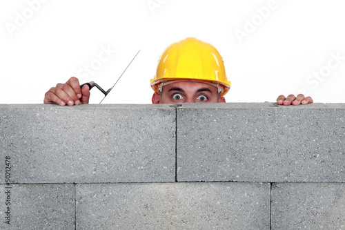 Workers peeking behind wall