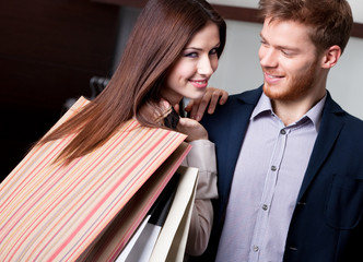 Happy woman with boyfriend after shopping smiles
