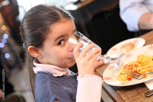 Little girl eating meal in restaurant
