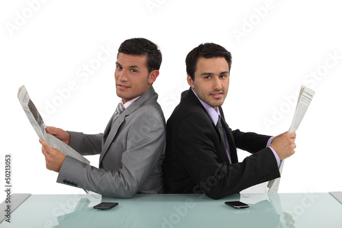 Two businessmen reading the newspaper