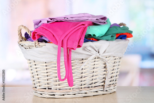 Clothes in wooden basket on table in room