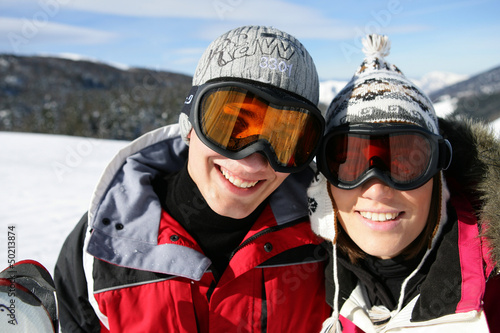 Skiing couple laying in the snow