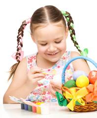 Little girl preparing eggs for Easter