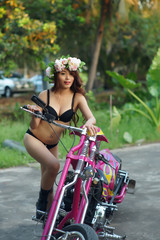 Young sexy Asian woman in black lingerie on pink motorcycle