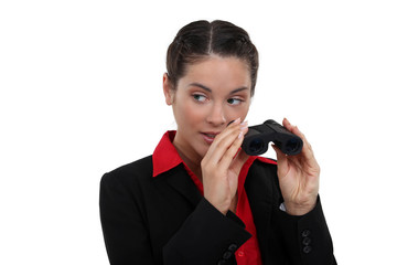 Curious brunette holding binoculars