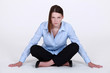 Stern businesswoman sitting cross legged