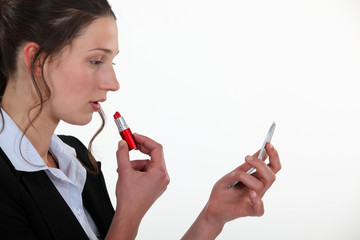 A businesswoman putting lipstick on.