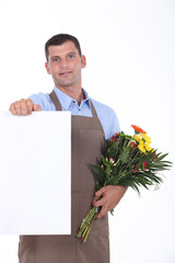 Man with bouquet of flowers and poster
